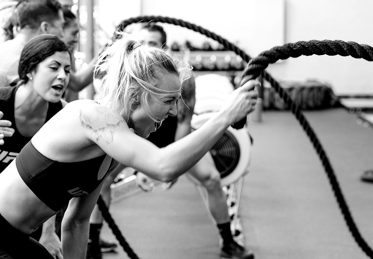 Coach cheering member on moving fitness rope in daily ultimate training class